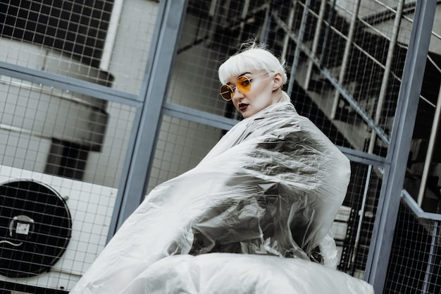 Ecology concept. girl with plastic wrap. city style. urban photo