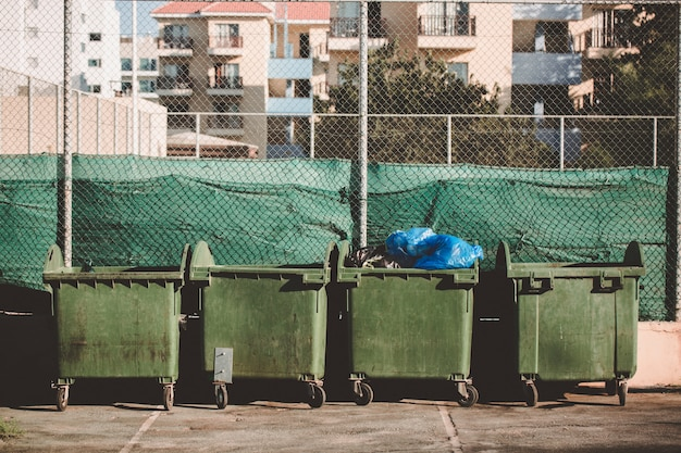 Ecology concept. green metal trashcan with waste. large plastic wheelie bins for rubbish, recycling and garden waste