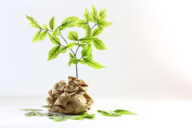 Экологическая концепция. маленький завод в переработанной бумаге на белом фоне