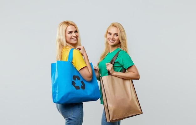 Концепция экологии. молодые женщины в повседневной одежде держат на плечах экологические переработанные продуктовые сумки.