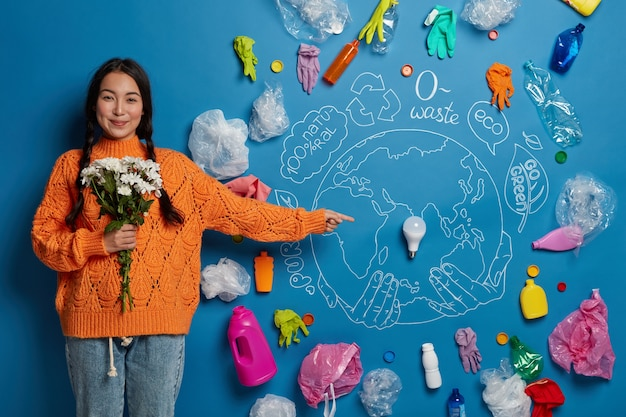 Ecology, energy consumption and pollution concept. pleased female with flowers demonstrates drawn planet and recyclable waste around, being eco activist