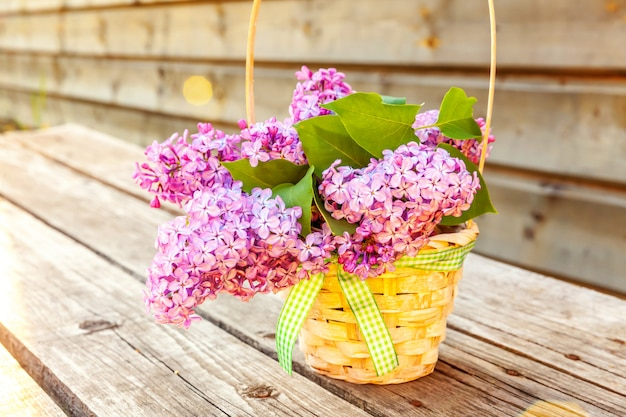 Ecology nature springtime concept. bouquet of flowers beautiful smell violet purple lilac in vase on rustic wooden background. inspirational natural floral spring blooming garden or park.