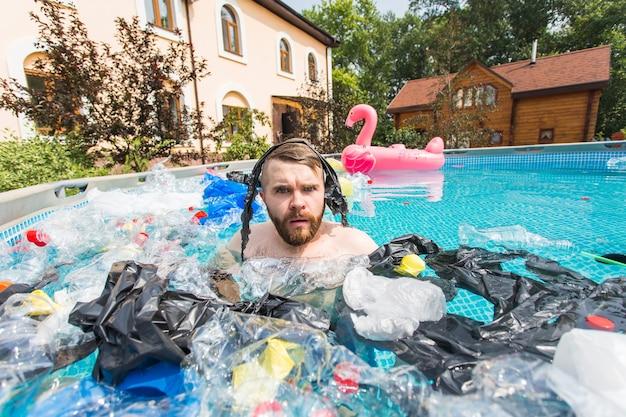生態学、プラスチックごみ、環境緊急事態、水質汚染 – ショックを受けた男性が汚れたプールで泳ぐ。