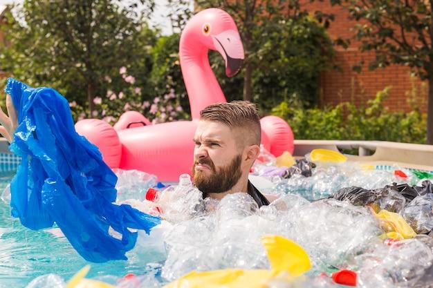 生態学、プラスチックごみ、環境緊急事態、水質汚染 – ショックを受けた男性が汚れたプールで泳ぐ。 Premium写真