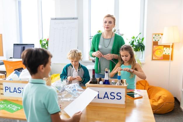 Экологический проект. темноволосый школьник представляет свой экологический проект одноклассникам и учителю