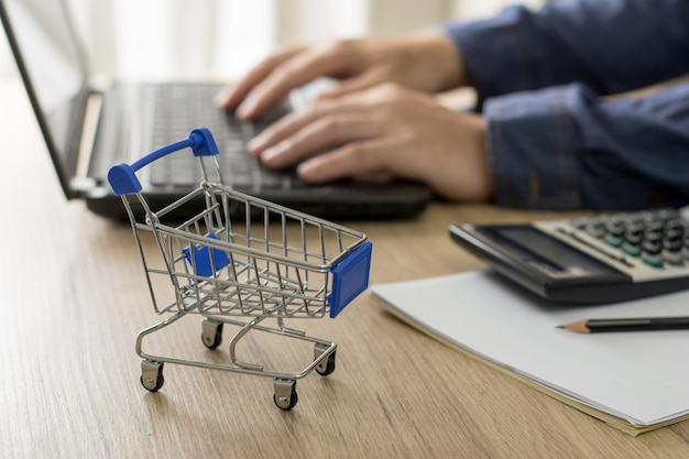 Eコマースとオンラインビジネスの概念。木製のテーブルの上のショッピングカートとバックグラウンドで顧客とチャットするためにコンピューターを使用している男性。