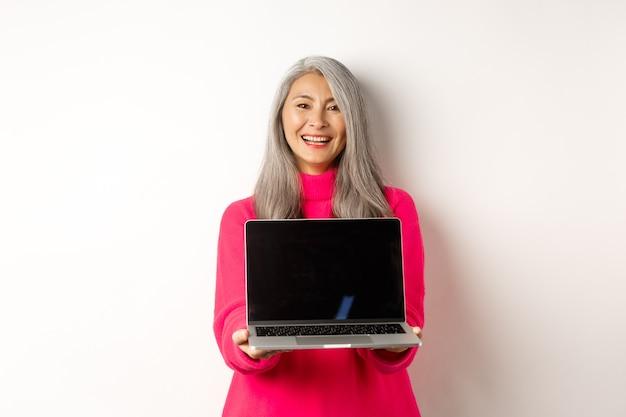 空白のノートパソコンの画面と笑顔のスタンドを示すeコマースのコンセプト美しいアジアのシニア実業家...