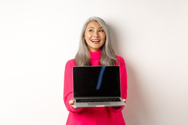 Eコマースのコンセプト幸せな美しいアジアの年配の女性と灰色の髪を脇に見て笑顔のshowin ...
