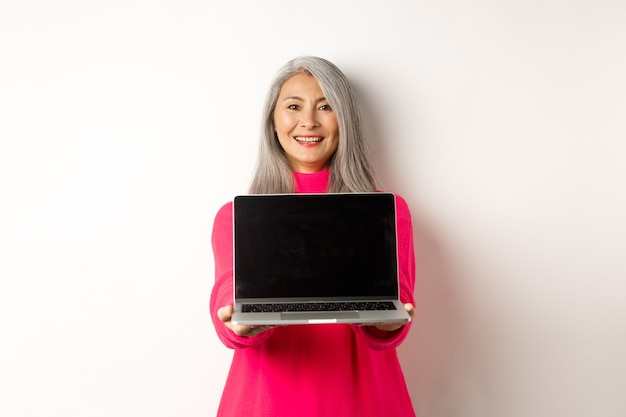 전자 상거래 개념은 빈 노트북 화면을 보여주고 행복한 데모를 보고 웃는 아시아 노인 여성입니다.