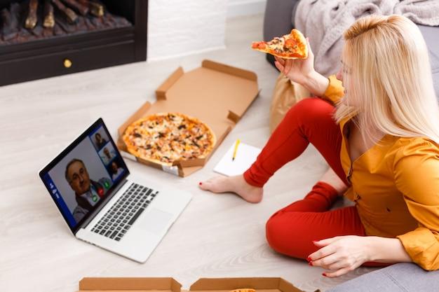 Eコマースの女性。オンラインショッピング、床に座ってピザを食べるためにコンピューターを使用している若い女性。