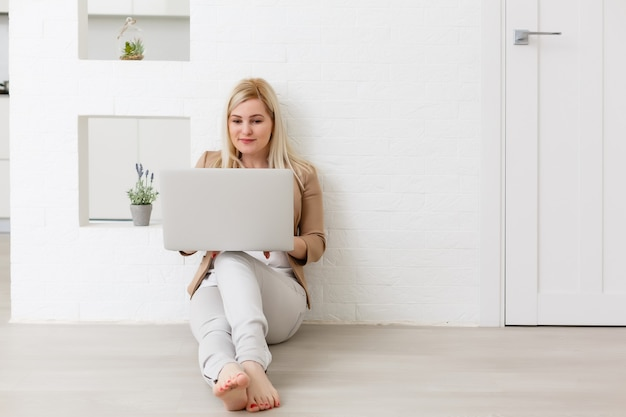 Eコマースの女性。床に座って、オンラインショッピングにコンピューターを使用して若い女性