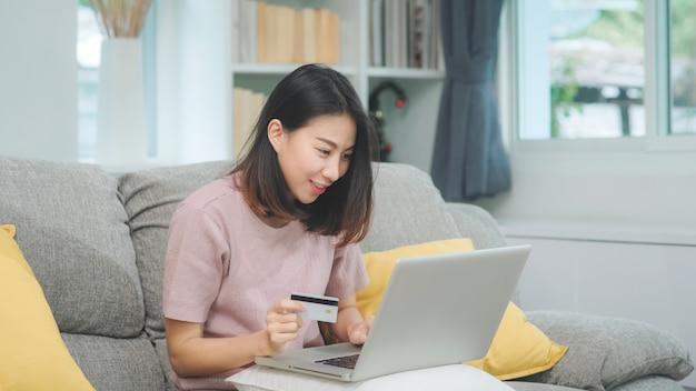 Азиатская женщина используя ecommerce покупок компьтер-книжки и кредитной карточки, женщина ослабляет чувствовать счастливые онлайн покупки сидя на софе в живущей комнате дома. образ жизни женщины отдыхают дома концепции.