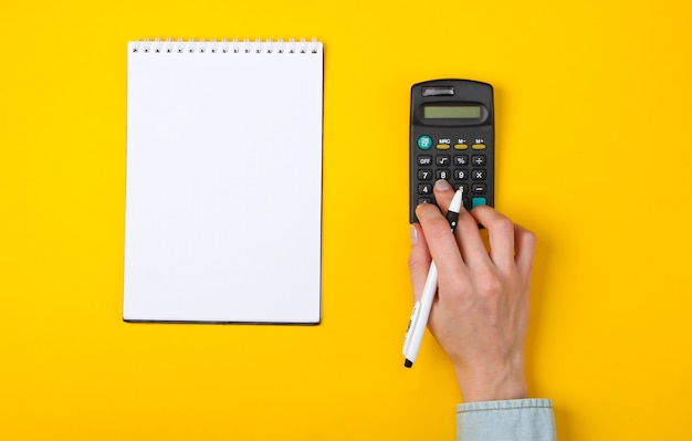 Economic analysis. female hands use calculator on a yellow with a notebook