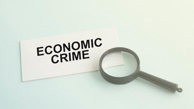 Economic crime word on white paper card and magnifying lens