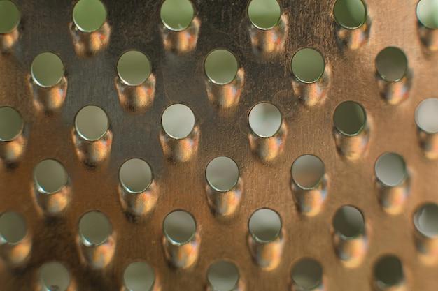 何かをこすったり、すりつぶしたりするための小さな穴が開けられた金属板の形の経済的な装置
