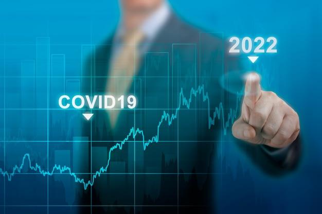 2022年の景気回復。covid19パンデミックによって引き起こされた危機後の世界的な景気回復のタイムラインチャート図。濃い青でグラフの成長計画を指すビジネスマン。危機後に経済を再開する