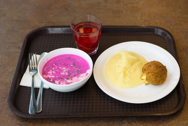 쟁반에 으깬 감자 칠면조 커틀릿과 차가운 비트 뿌리 수프의 경제적인 점심