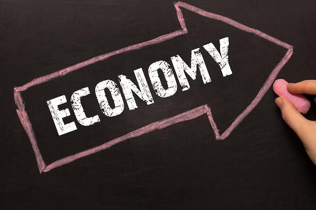 Economy - chalkboard with arrow on black background