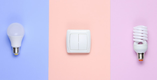 Economy light bulbs, the switch on the pastel background. top view. minimalism electro consumer concept