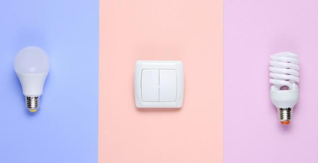Лампочки эконом, выключатель на пастельном фоне. вид сверху. потребительская концепция минимализма