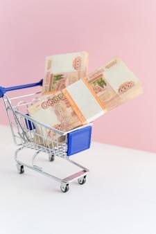 Корзина с банкнотами на розовом фоне. финансовая концепция. концепция покупок онлайн. мультивалютная корзина, бизнес, финансы, economy.money в корзине покупок. черная пятница распродажа