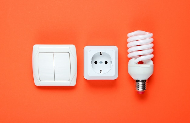 Economy spiral light bulb, electric plug, switch. top view. minimalism electro consumer concept