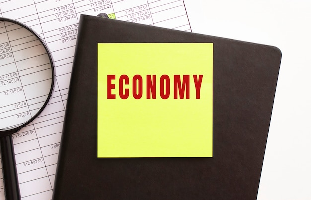 Economy text on a sticker on your desktop. diary and magnifier. financial concept.