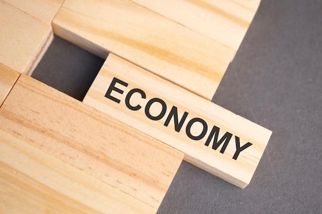 黄色の背景の木製ブロックに経済の言葉。ビジネス倫理の概念。