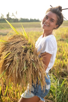 Ecotourism or daily work. happy woman farmer during harvesting on the rice field