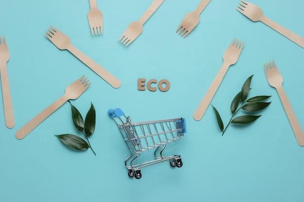 Эко-вегетарианские покупки торговая тележка деревянные вилки зеленые листья на синем пастельном фоне
