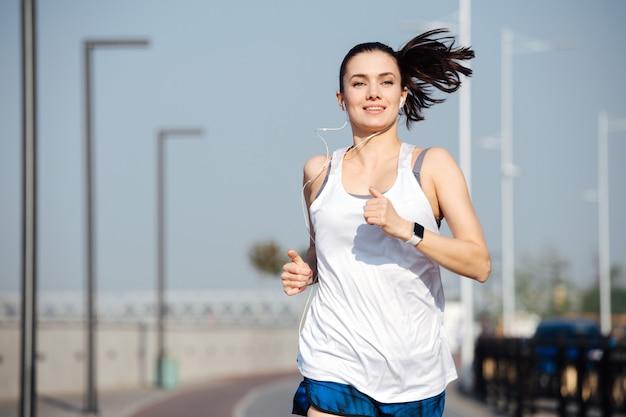 야외 트랙에서 달리는 황홀한 운동 여자. 흐리게 배경입니다. 맑고 푸른 하늘 아래 화창한 날. 그녀는 흰색 민소매 셔츠와 미니 반바지를 입고 있습니다.