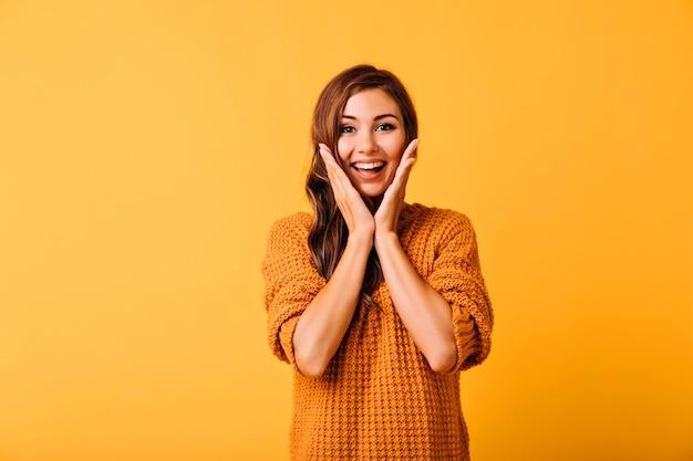 Bella donna estatica che tocca il suo fronte. ritratto dello studio della ragazza spensierata sorridente isolata su colore giallo.