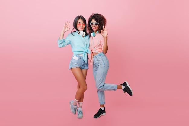 유럽 슬림 친구 근처 점프 스포츠 신발에 황홀 할 정도로 흑인 여성. 면 셔츠에 혼혈 아가씨와 자유 시간을 즐기는 우아한 아시아 소녀.
