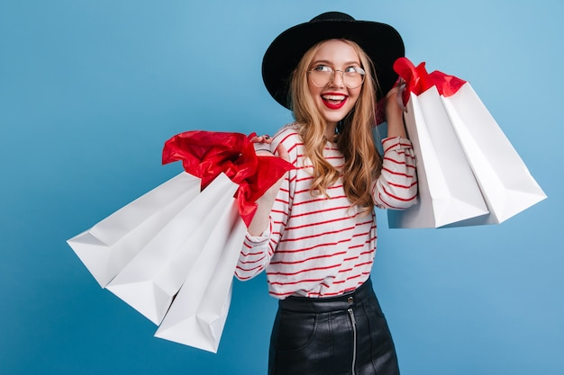 Ragazza bionda estatica con borse della spesa che esprimono felicità. splendida donna caucasica in cappello in piedi su sfondo blu.