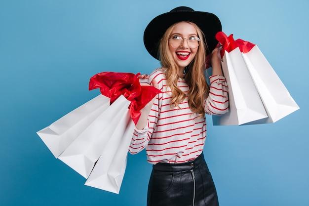 幸せを表現する買い物袋を持つ恍惚としたブロンドの女の子。青い背景の上に立っている帽子のゴージャスな白人女性。