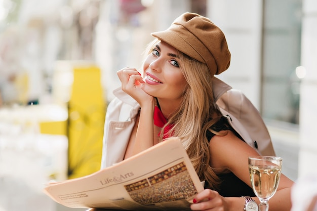 Ecstatic blue-eyed girl laughing while resting in outdoor restaurant with glass of wine and daily newspaper. smiling young woman wears stylish cap having fun after work relaxing in cafe.