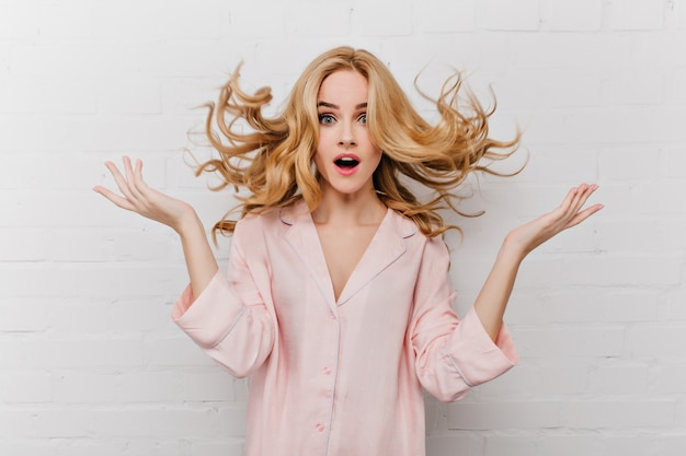 흰색 벽돌로 벽 앞에서 포즈를 취하는 긴 금발 머리를 가진 황홀한 파란 눈의 여자. 아름 다운 분홍색 잠 옷에 놀란 된 여자의 실내 샷.