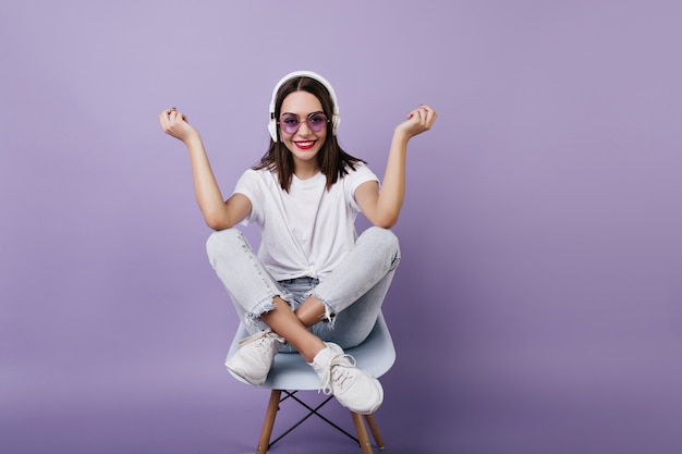 Signora dai capelli castani estatica divertente in posa durante l'ascolto della canzone preferita. tiro al coperto di bella ragazza europea in abito bianco seduto sulla sedia.