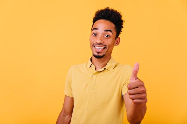미소로 포즈를 취하는 밝은 여름 옷에 황홀한 갈색 머리 남자. 엄지 손가락을 보이고 웃고 기쁜 아프리카 모델의 실내 샷.
