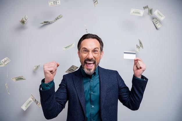 Восторженный деловой человек держит кредитную карту, поднимает кулак с летающими долларами