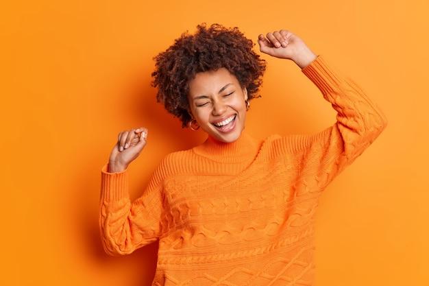 Восторженная беззаботная женщина с афро-волосами танцует с поднятыми руками, широко улыбается, делает жест победителя, празднует триумф в оранжевом джемпере, позирует в помещении