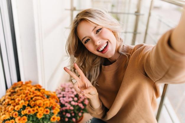 평화 기호 셀카를 만드는 황홀한 caucaisan 여자. 오렌지 꽃과 함께 포즈를 취하는 우아한 곱슬 소녀.