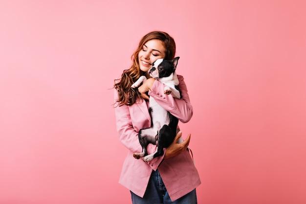 Восторженная кавказская девушка в модной куртке охлаждает с собакой. крытый портрет модной рыжеволосой дамы, позирующей с французским бульдогом.
