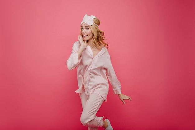 Ragazza riccia estatica in pigiama di seta che salta sulla parete luminosa. signora emotiva in maschera per dormire divertendosi con interni rosa.