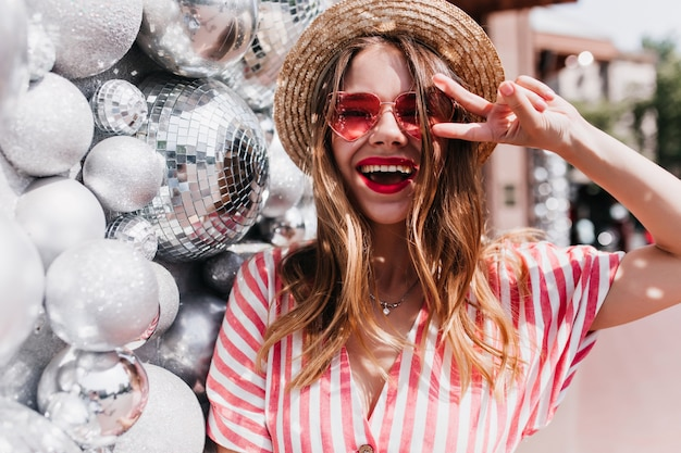 Восторженная европейская девушка смеется, позируя рядом с блестящими шарами. открытый портрет красивой добродушной дамы в соломенной летней шляпе.