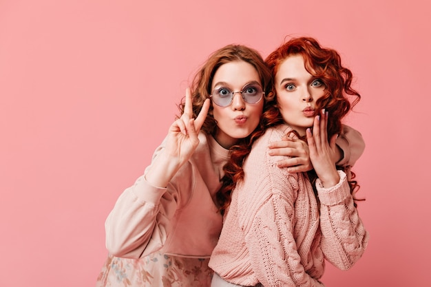 평화 기호를 보여주는 황홀한 유럽 소녀. 분홍색 배경에 껴안은 두 꿈꾸는 숙 녀의 스튜디오 샷.