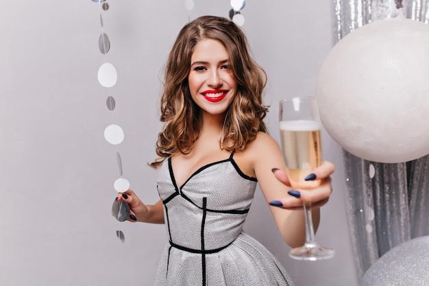誠実な笑顔でワイングラスを上げる赤い口紅を持つ恍惚としたヨーロッパの女性。新年のお祝いの間に身も凍るようなスタイリッシュなパーティードレスを着た素敵な女の子の屋内の肖像画。