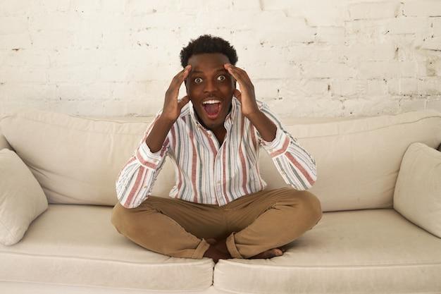 Estatico eccitato giovane maschio africano seduto in soggiorno tenendo le mani sulla sua testa, esclamando wow, omg, essendo impressionato