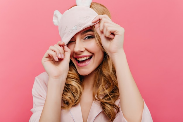 Ecstatic fair-haired lady having fun early in morning. charming european girl in funny eyemask laughing on pink wall.