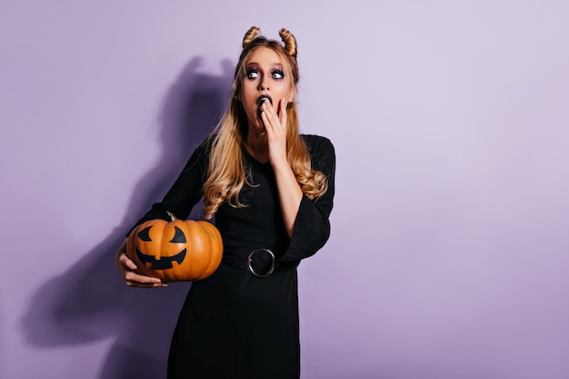 Ecstatic female vampire thinking about something evil. witch in black dress holding pumpkin.